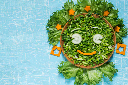 The concept of ecology, healthy food, preventing the spring avitaminosis - fresh green vegetables in the form of a smiling face. Symbol Earth Day