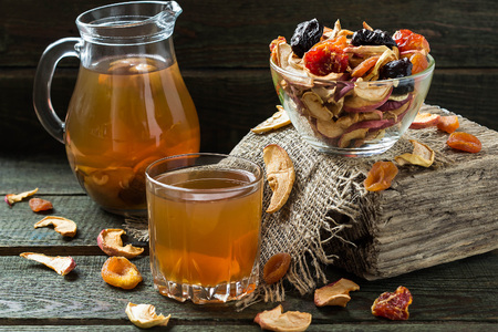 apricots: Compote of dried fruits in the jug and mug and assorted dried fruits in bowl on wooden table. Selective focus
