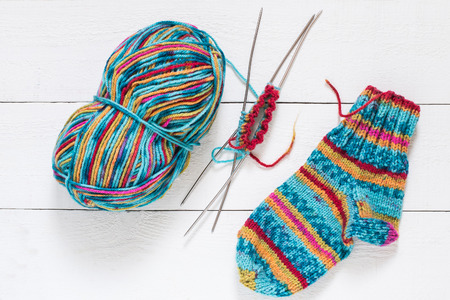 skein: Skein of multi-colored yarn, beautiful knitted socks, knitting with spokes on white wooden table Stock Photo