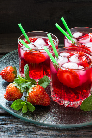 cocktail glasses: Three glasses of cold refreshing drink with strawberries, ice and cocktail straws on a glass tray with fresh strawberries and mint Stock Photo