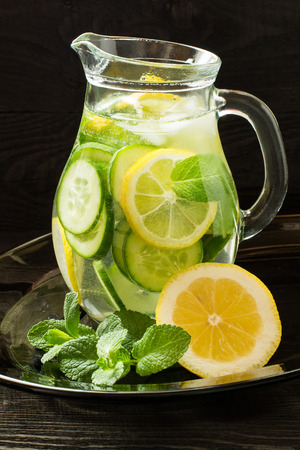 Fresh cold water with lemon, cucumber, ginger, mint and ice in a pitcher on a glass tray