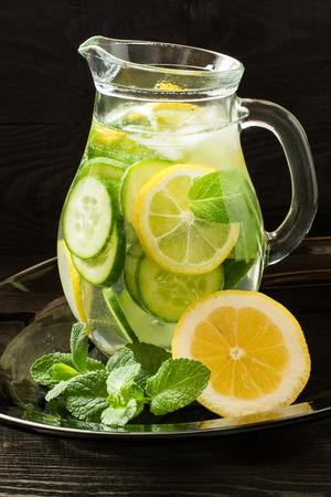 Vers koud water met citroen, komkommer, gember, munt en ijs in een kruik op een glazen bak