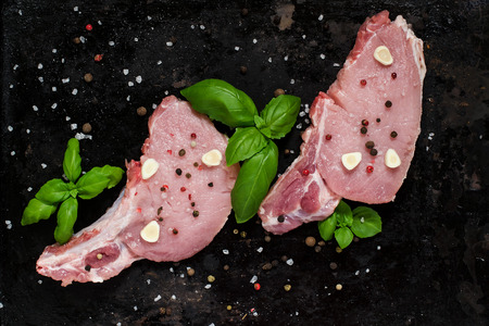 loin chops: Fresh pork loin chops with spices and basil on the old dark background