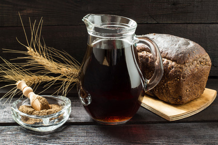 satisfies: Traditional Russian drink kvass made from bread, rye malt, sugar and water. Kvass in the jug, rye bread and malt in a bowl with scoop on a dark wooden background. Selective focus