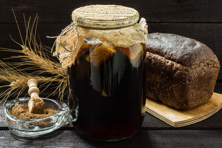 satisfies: Traditional Russian drink kvass made from bread, rye malt, sugar and water. Kvass in the jar is closed with gauze, rye bread and malt in a bowl with scoop on a dark wooden background. Selective focus Stock Photo