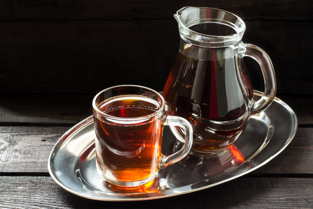 satisfies: Traditional Russian drink kvass made from bread, rye malt, sugar and water. Kvass in the jug and mug on a dark wooden background Stock Photo