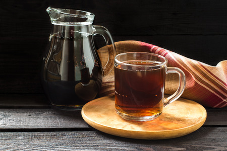 satisfies: Traditional Russian drink kvass made from bread, rye malt, sugar and water. Kvass in the jug and mug on a dark wooden background. Selective focus Stock Photo
