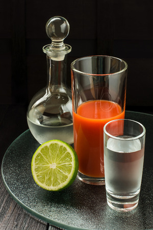 highball: Ingredients for bloody mary cocktail: vodka in a decanter and a glass, tomato juice in a highball on a glass tray