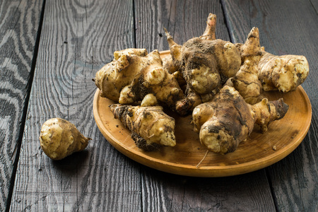 inulin: Fresh organic jerusalem artichoke (Helianthus tuberosus) with soil particles on a round wooden board