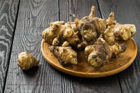 Fresh organic jerusalem artichoke (Helianthus tuberosus) with soil particles on a round wooden board Stok Fotoğraf - 55032478