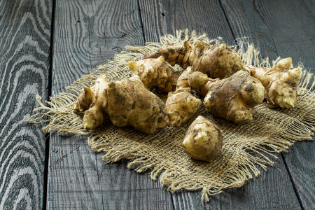 jerusalem artichoke: Fresh organic jerusalem artichoke (Helianthus tuberosus) with soil particles on sackcloth