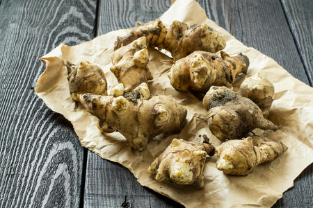 jerusalem artichoke: Fresh organic jerusalem artichoke (Helianthus tuberosus) with soil particles on the packaging paper. Selective focus Stock Photo