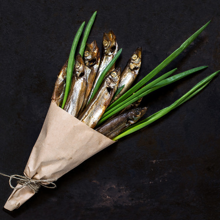 cornet: Smoked capelin with green onions in paper cornet on an old iron background. Top view