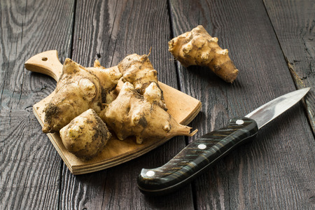 jerusalem artichoke: Fresh organic jerusalem artichoke (Helianthus tuberosus) with soil particles on a wooden board