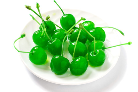 maraschino: Green maraschino cherry on a plate on a white background
