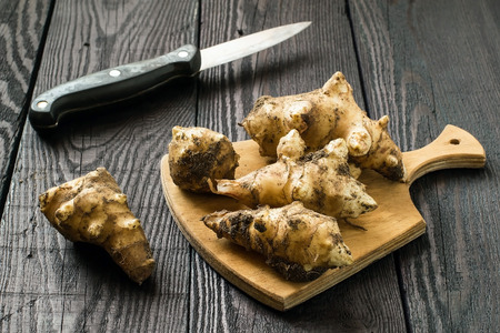 inulin: Fresh organic jerusalem artichoke (Helianthus tuberosus) with soil particles on a wooden board