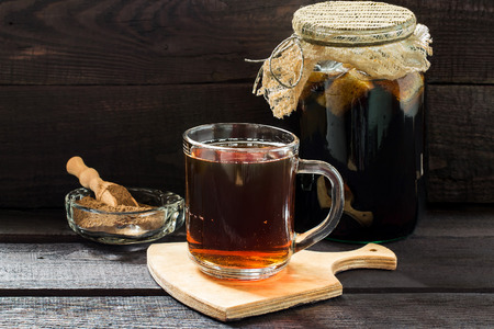 satisfies: Traditional Russian drink kvass made from bread, rye malt, sugar and water. Kvass in the jar, rye malt in a bowl with scoop on a dark wooden background. Selective focus Stock Photo