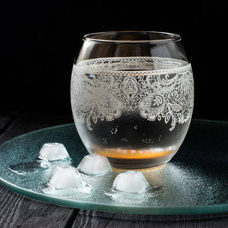 relieved: Cold pure mineral water in a beautiful glass with ornaments on the dark background. Square image