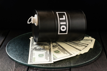 hydrocarbon: Oil business concept. Barrel of oil on dollar bills  on a dark wooden background