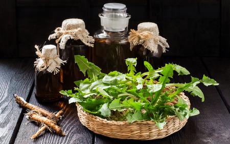 Medicinale planten - paardenbloem. Paardebloem bladeren in een mand, tinctuur en siroop in de farmaceutische flessen, wortels op houten achtergrond. Het wordt gebruikt voor kruidengeneeskunde en gezonde voeding