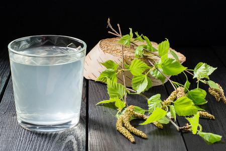 Koud vers berkensap in een glazen en berken takken op een donkere achtergrond Stockfoto