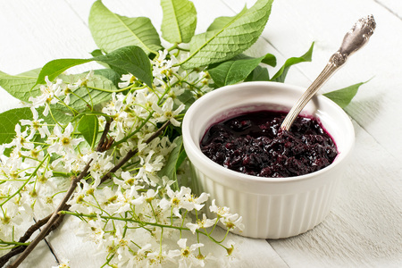 diuretic: Medicinal plant - bird cherry (Prunus padus). Flowering branches and jam on a white wooden background
