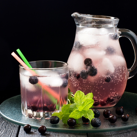 water jug: Cold refreshing drink with blueberries, black currants, juice, soda water and ice in a jug and a glass of cocktail straws on a dark background. Square image