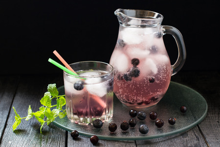 Cold refreshing drink with blueberries, black currants, juice, soda water and ice in a jug and a glass of cocktail straws on a dark background. Selective focus