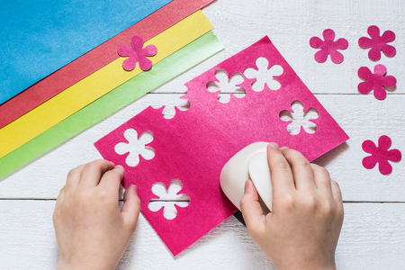 paper punch: The child makes special hole punch flowers of pink paper. Sheets of paper and cut out flowers on white wooden table Stock Photo