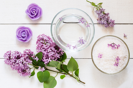 perfumed candle: Flower SPA concept: bath with flower water, sea salt, aromatic candle and lilac flowers on white wooden table. Top view