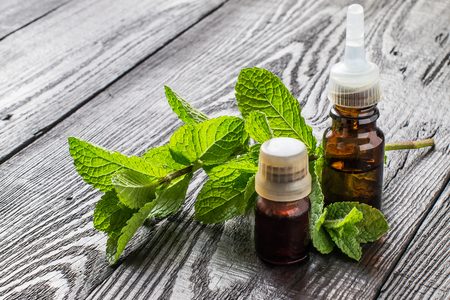 Mint essential oil in small brown bottles and fresh mint on a dark wooden table Stock Photo