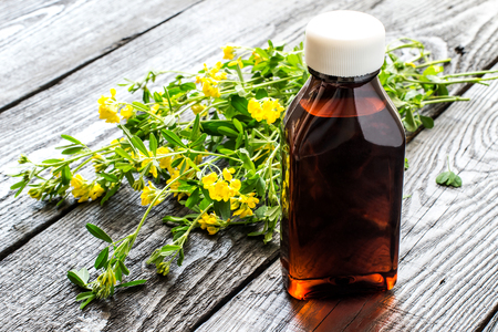 antispasmodic: Medicinal plant Common Birds-foot Trefoil (Lotus corniculatus) and pharmaceutical bottle on a dark wooden table. Used in herbal medicine before flowering (flowering plant poisonous), honey plant. Selective focus Stock Photo