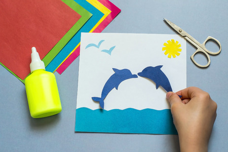 Kind dat de applicatie op het mariene thema. Het idee voor de creativiteit van kinderen, een kunstproject van papier. Vellen gekleurd papier, lijm, schaar Stockfoto
