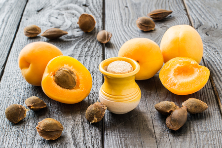Essential oil from apricot kernels in a small yellow clay jar, fresh apricots and apricot seeds on a dark wooden table