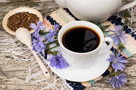 Medicinale plant cichorei: bloemen en gemalen wortels. De wortels van de planten worden gebruikt als vervanging voor koffie. Drink uit cichorei in een kop op de oude houten tafel. Rustieke stijl, selectieve aandacht