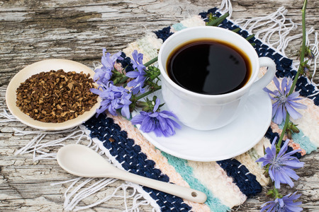 chicory coffee: Medicinal plant chicory: flowers and ground roots. The roots of the plants are used as a substitute for coffee. Drink from chicory in a cup on the old wooden background. Rustic style, selective focus