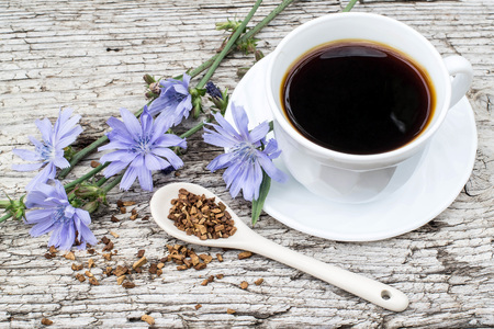 acuminate: Medicinal plant chicory: flowers and ground roots in the spoon. The roots of the plants are used as a substitute for coffee. Drink from chicory in a cup on the old wooden background Stock Photo