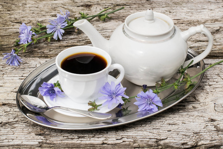 inulin: Medicinal plant chicory. The roots of the plants are used as a substitute for coffee. Drink from chicory in a cup and teapot on a metal tray on the old wooden background. Rustic style