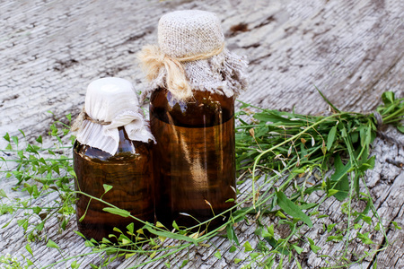 pharmaceutical bottle: Medicinal plant shepherds purse (Capsella bursa-pastoris) and brown pharmaceutical bottle on old wooden table. Used in herbal medicine, healthy eating, as well as for cosmetics purposes