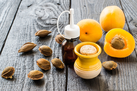 apricot kernels: Essential oil from apricot kernels in small brown bottles and small yellow clay jar, fresh apricots and apricot seeds on a dark wooden table