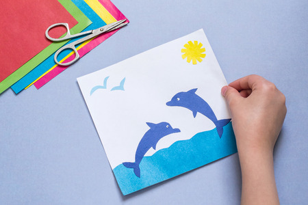 paper art projects: Paper applique is made by the child on a sea theme. The idea for childrens creativity, an art project made of paper. Sheets of colored paper, glue, scissors. Childrens hand holding a picture