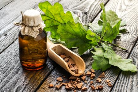 薬用植物オーク (コナラ)。支店、チンキ、暗い木製のテーブルのスクープでオークの樹皮。漢方薬の樹皮、葉とドングリ (コーヒーの代用として使用