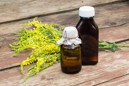 antispasmodic: Melilotus officinalis, known as yellow sweet clover, yellow melilot, ribbed melilot, common melilot and pharmaceutical bottles on old wooden table. Used in herbal medicine, is a major source of nectar