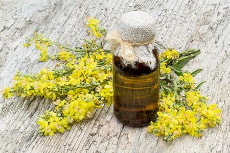 Toorts, ook wel bekend als fluweel plant (Verbascum) en farmaceutische fles op oude houten tafel. De plant wordt zeer gewaardeerd in de kruidengeneeskunde, wordt het gebruikt in de vorm van infusies, afkooksels, zalven, oliën Stockfoto