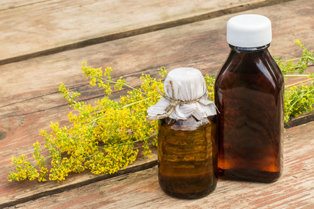 Medicinal plant Galium verum (ladys bedstraw, yellow bedstraw) and pharmaceutical bottle on old wooden table. Used in herbal medicine, good honey plant. Previously it used in the manufacture of cheese 版權商用圖片