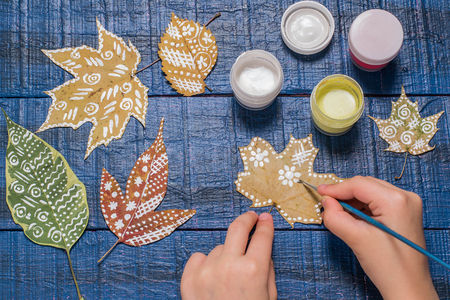 Girl paints patterns yellow maple leaf. Gouache, brush and various autumn leaves on a blue wooden table. Childrens art project. Colorful Hand-painted on dry autumn leaves
