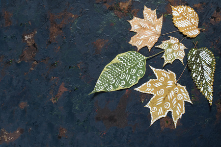 dry leaf: Hand painted on dry autumn leaves. Beautiful autumn background with leaves on the old blue iron surface with copy space