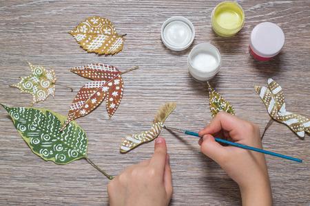 Mädchen malt Doppel samara Ahorn gemustert. Gouache, Pinsel und verschiedene Blätter im Herbst auf einem Holztisch. Kinderkunstprojekt. Bunte handgemalt auf trockenen Blätter im Herbst Lizenzfreie Bilder