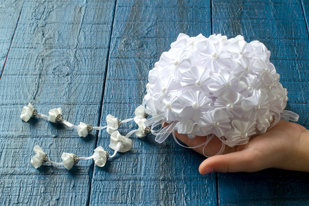 kanzashi: Making beautiful bows for decoration hair and gifts in the art kanzashi. Step by step photo instructions. Step 6. Ready bow of the details in the shape of a flower with pendants in a childs hands Stock Photo