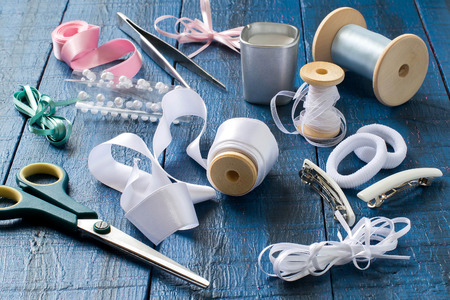 barrettes: Making beautiful bows for decoration hair and gifts in the art kanzashi. Step by step photo instructions. Step 1. Preparation of materials (tape, rubber, barrettes) and tools (scissors, tweezers) Stock Photo